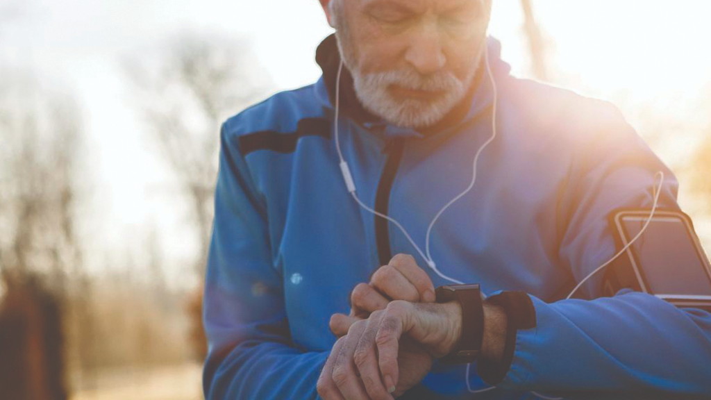 A man checking their smart watch while exercising and listening to music.